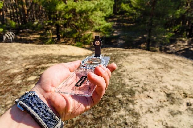 Reisender auf der suche nach dem richtigen weg im wald mit kompass