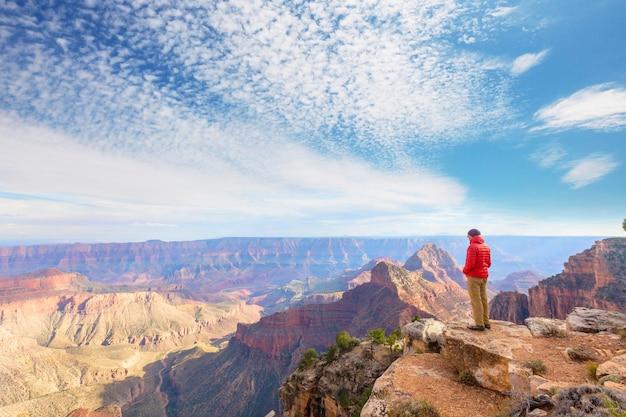 Reisender auf klippenbergen über grand canyon national park, arizona, usa. inspirierende emotionen. reisen lifestyle reise erfolgsmotivation konzept abenteuerurlaub outdoor-konzept.