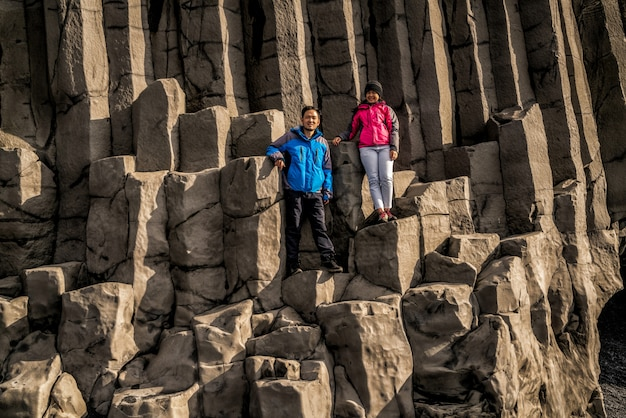 Reisender auf sechseckigen felsen in vik, island.