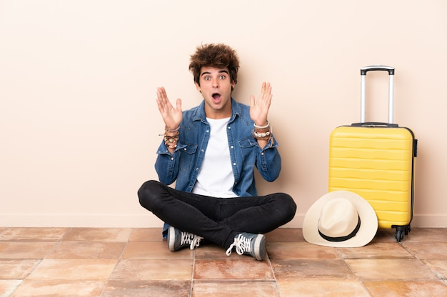 Reisender bemannen seinen koffer, der auf dem boden mit überraschungsgesichtsausdruck sitzt