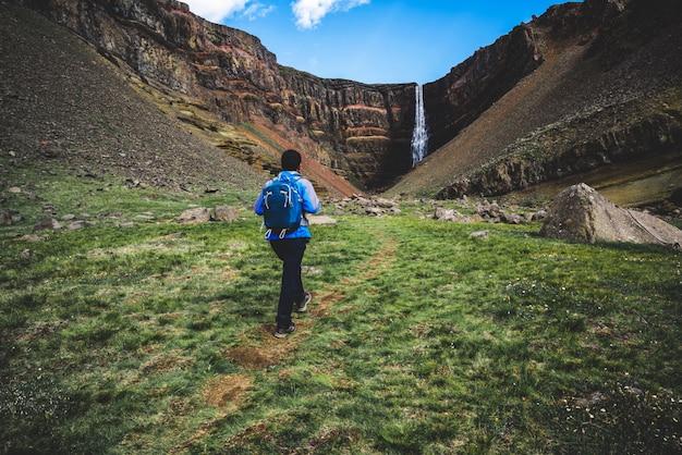 Reisender, der am hengifoss wasserfall, island wandert.