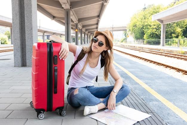 Reisender, der auf einen zug mit ihrem gepäck wartet