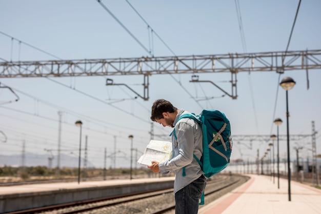 Reisender, der auf einer karte auf station platfom schaut