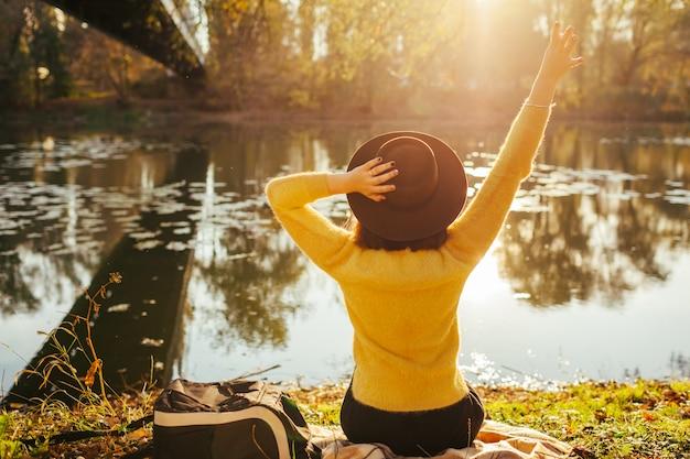 Reisender, der durch herbstfluß bei sonnenuntergang sich entspannt. tourist der jungen frau, der auf bank sitzt und den hut anhebt hände hält