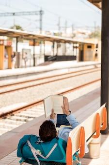 Reisender, der ein buch liest und auf zug wartet