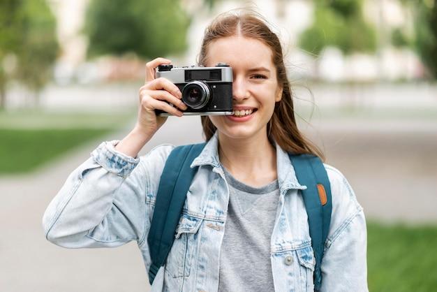 Reisender, der ein foto mit retro-kamera macht