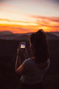 Reisender, der eine fotografie des sonnenuntergangs macht