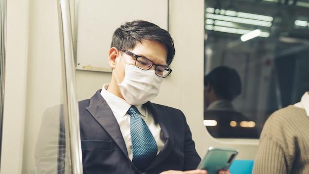 Reisender, der gesichtsmaske trägt, während handy im öffentlichen zug benutzt. coronavirus-krankheit oder covid 19-pandemie-ausbruch und städtisches lebensstilproblem im pendelkonzept der hauptverkehrszeit.