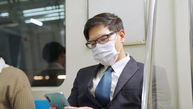 Reisender, der gesichtsmaske trägt, während handy im öffentlichen zug benutzt