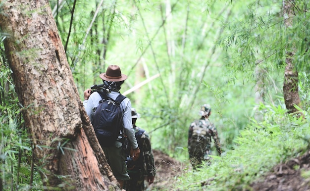 Reisender, der in den bambuswald geht mannwanderer-gebirgsgruppe freunde, die mit rucksäcken gehen