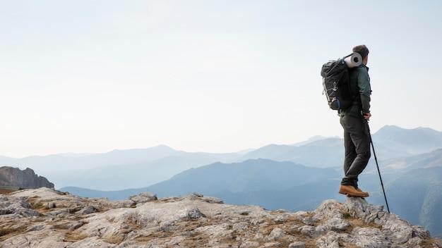 Reisender, der in den bergen wandert, während er seine wichtigsten sachen im rucksack hat