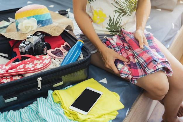 Reisender der jungen frau, der ihre kleidung und material im koffer verpackt