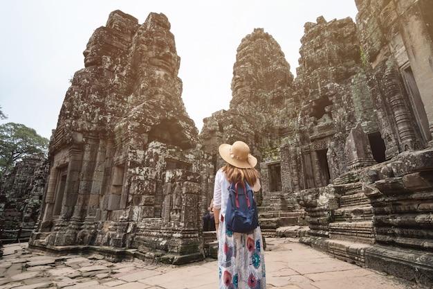 Reisender der jungen frau, der in bayon-tempel an angkor wat komplex besucht
