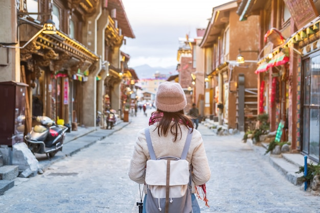 Reisender der jungen frau, der in die alte stadt, shangri-la, reiselebensstilkonzept geht