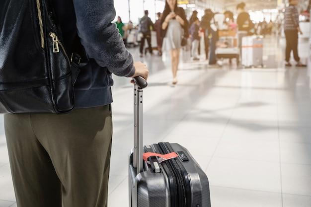 Reisender der jungen frau, der in flughafenterminalhale geht