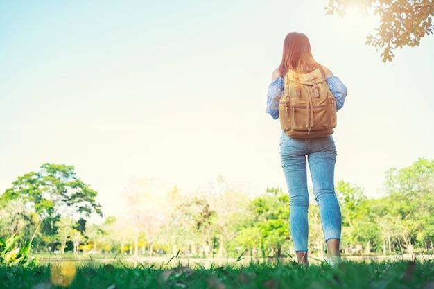 Reisender der jungen frau, der mit sonnenlicht im freien steht