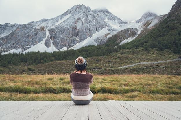 Reisender der jungen frau, der schöne landschaft sitzt und schaut und einsam sich fühlt, reiselebensstilkonzept