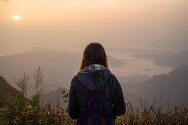 Reisender der jungen frau, der sonnenaufgang betrachtet