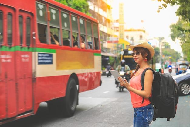 Reisender der jungen frau mit schwarzem rucksack und hut, die karte auf der tablette in bangkok betrachtet. reise-konzept