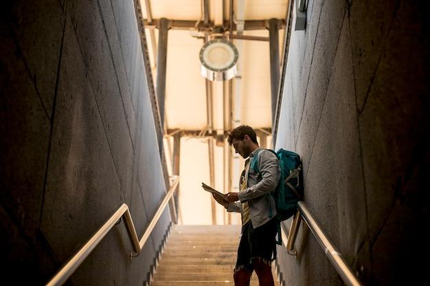 Reisender, der karte auf treppe betrachtet