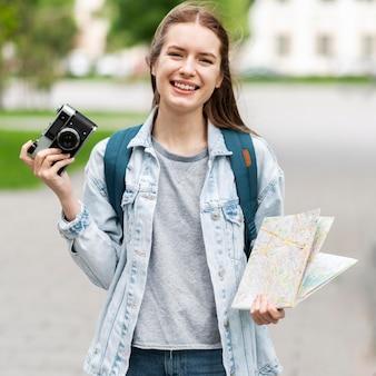 Reisender, der karte und altes kamerafoto hält