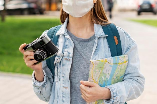 Reisender, der medizinische maske hält karte und kamera hält