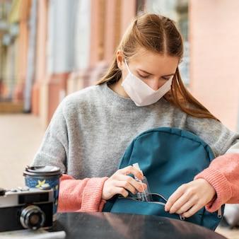 Reisender, der medizinische maske mit desinfektionsmittel trägt