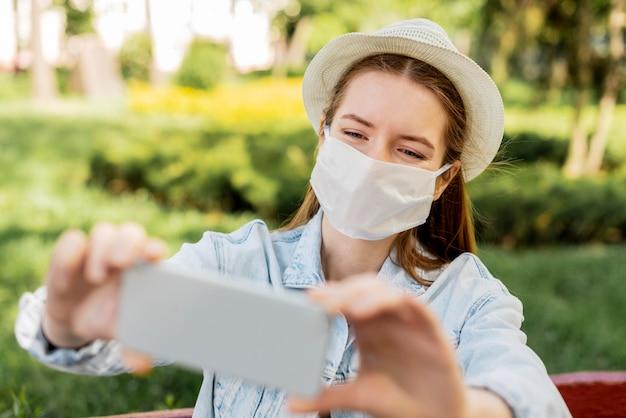 Reisender, der medizinische maske trägt, die ein selbstfoto macht
