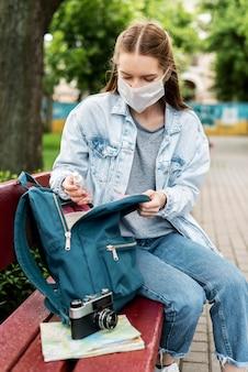 Reisender, der medizinische maske trägt, die eine retro-kamera hat