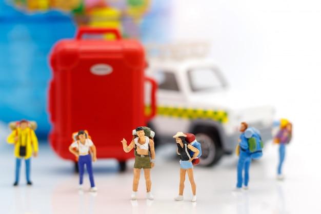 Reisender, der mit kugel und tasche steht.