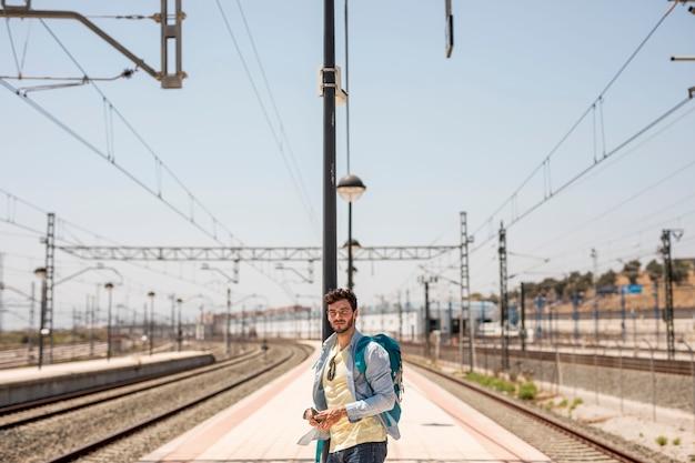 Reisender, der nach zug auf stationsplattform sucht