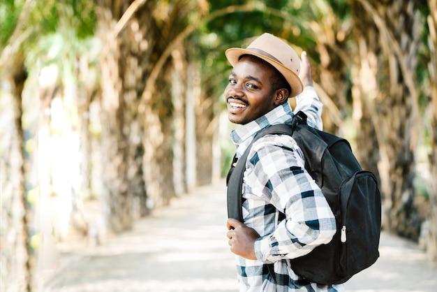 Reisender, der rucksack trägt, der durch den park geht