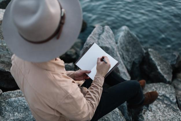 Reisender, der stilvollen hipsterhut trägt, der notizen schreibt und schöne landschaften genießt. abenteuerkonzept