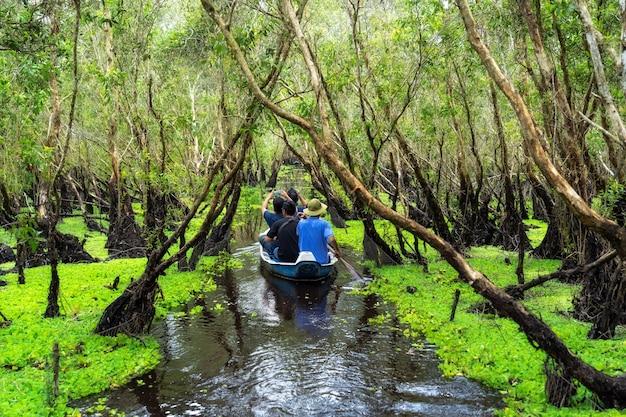 Reisender, der über dem traditionellen boot in tra su wald, mekong-delta-reise, vietnam besichtigt
