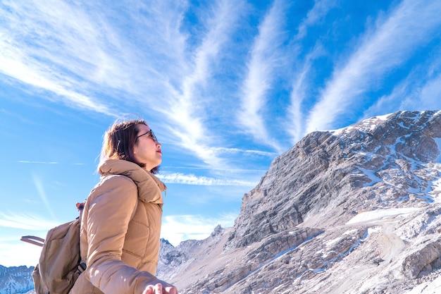 Reisender, der zum höchstberg auf blauem himmel und wolken deutschen alpen zugspitze betrachtet.