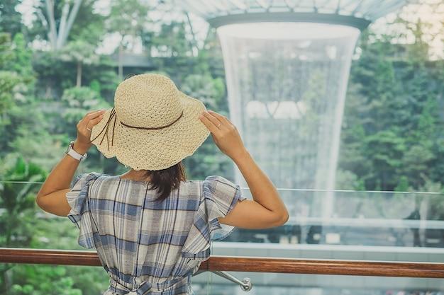 Reisender, der zum schönen regenwirbel am juwel changi-flughafen schaut