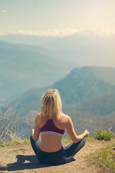 Reisender des jungen mädchens sitzt auf einen berg in einer yogahaltung.