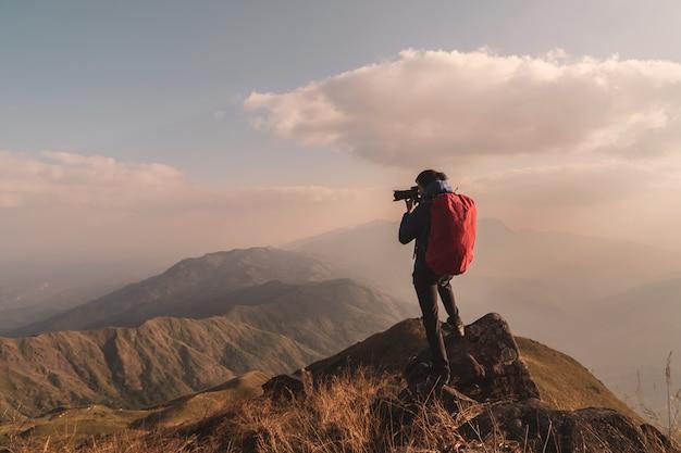 Reisender des jungen mannes mit dem rucksack, der ein foto auf berg macht