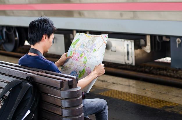 Reisender des jungen mannes mit karte auf straßenbauhintergrund