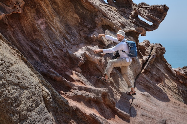 Reisender fotograf klettert auf felsen, um schöne natürliche ansicht, hormuz island, hormozgan, iran zu fotografieren.