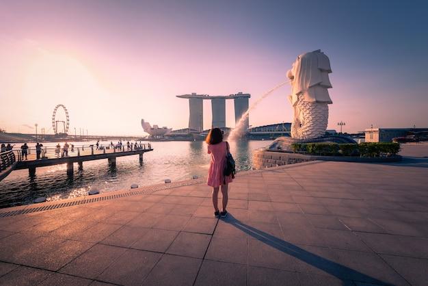 Reisender in den merlion park- und singapur-stadtskylinen bei sonnenaufgang