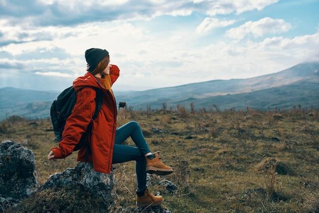 Reisender in roten jackenhüten mit rucksack sitzt auf einem stein in den bergen in der natur
