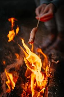 Reisender kocht köstliche würstchen am lagerfeuer wandern und camping im wald kochen am feuer
