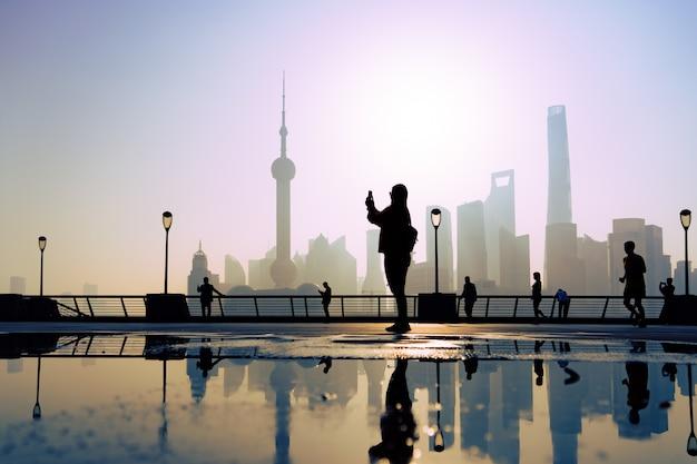 Reisender machen ein foto der morgenaktivität am bund, huangpu-flussufer, shanghai-stadt