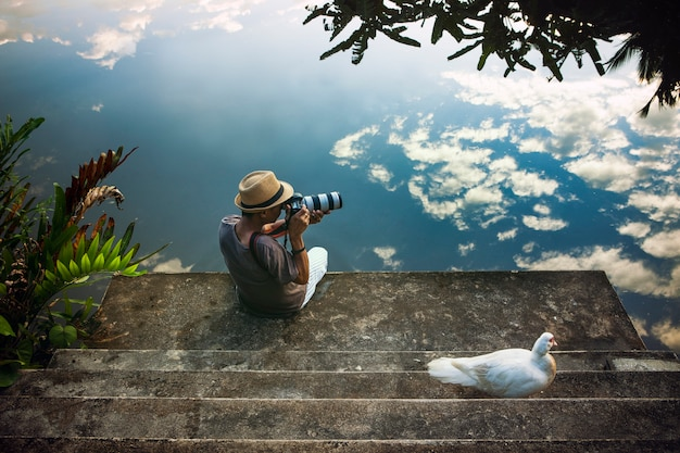 Reisender mann, der ein foto am alten pier gegen schöne reflexion des blauen himmels auf wasserboden macht