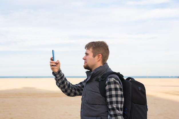 Reisender mann, der fotos zum strand mit smartphone-kamera in den sommerreiseferien oder zur wanderung nimmt