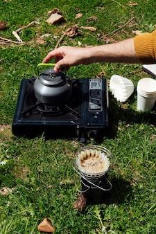 Reisender mann, der kaffee auf dem feld macht