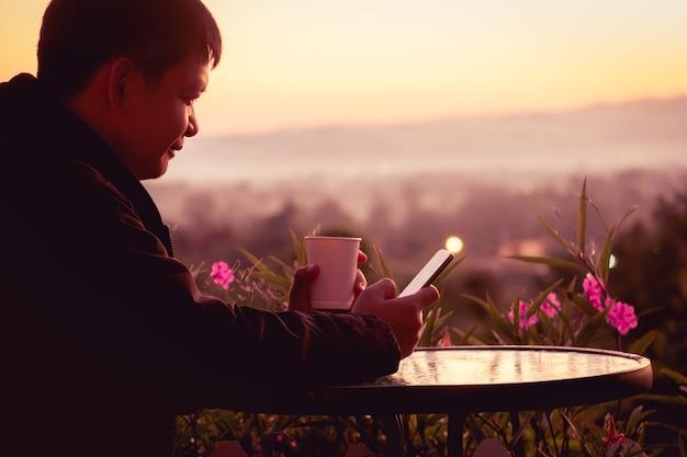 Reisender mann, der pullover trägt und eine tasse heißen kaffees mit smartphone hält