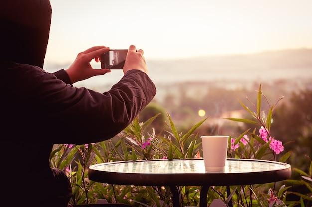Reisender mann, der pullover trägt und smartphone verwendet, um foto zu machen