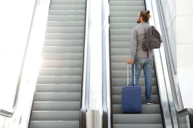 Reisender mann, der rolltreppe mit koffer und tasche geht